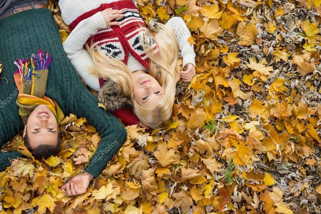 couple lying on autumn leaves at park
