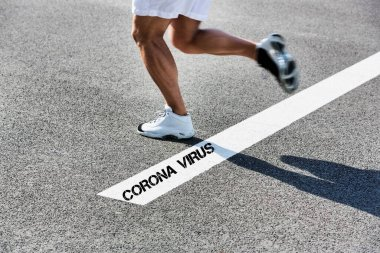 Athlete crossing the finishing line where the text of Corona Virus is written in black in