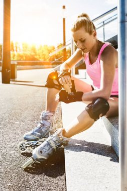 Young attractive woman adjusting safety gear while wearing rollerblades