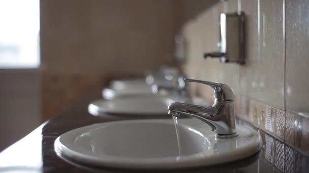 Egy vékony sugárban víz áramlik a törött csap.