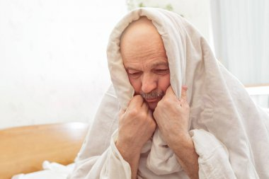 Sad elderly man suffers from insomnia.
