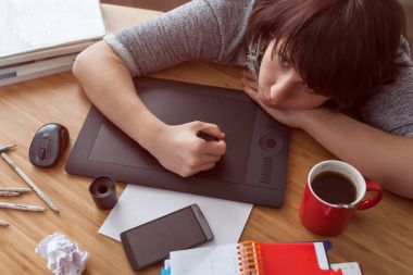 A girl draws a picture on a graphic tablet.
