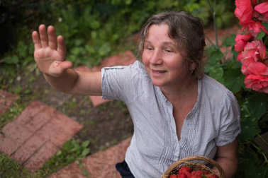 Cheerful mature woman sits in the garden and waving to friends