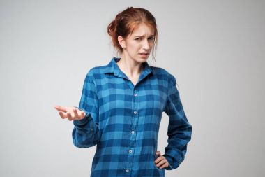 Portrait young angry woman in blue t-shirt. She is unhappy, annoyed by something.