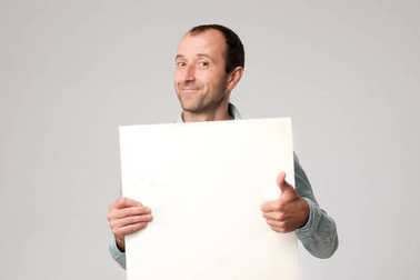 Hispanic man holds the blank sign in a studio white background.