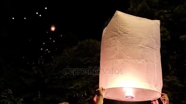 Lidé utíkají velké papírové lucerny s ohněm na noční obloze na oslavě Loi Krathong Yee Peng festivalu