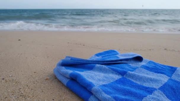 A homokos tengerparton kék törölköző