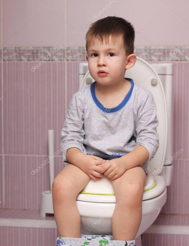 Niño sentado en el baño en el cuarto de baño — Fotos de ...