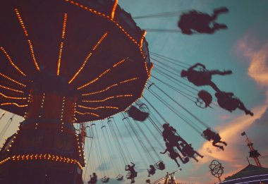 a local fair at dusk with people riding swinging rides and enjoy