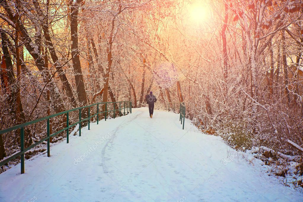 a man jogging down a snowy path in a local park with trees linin