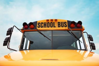 wide angle front view of a bright yellow orange school bus on a