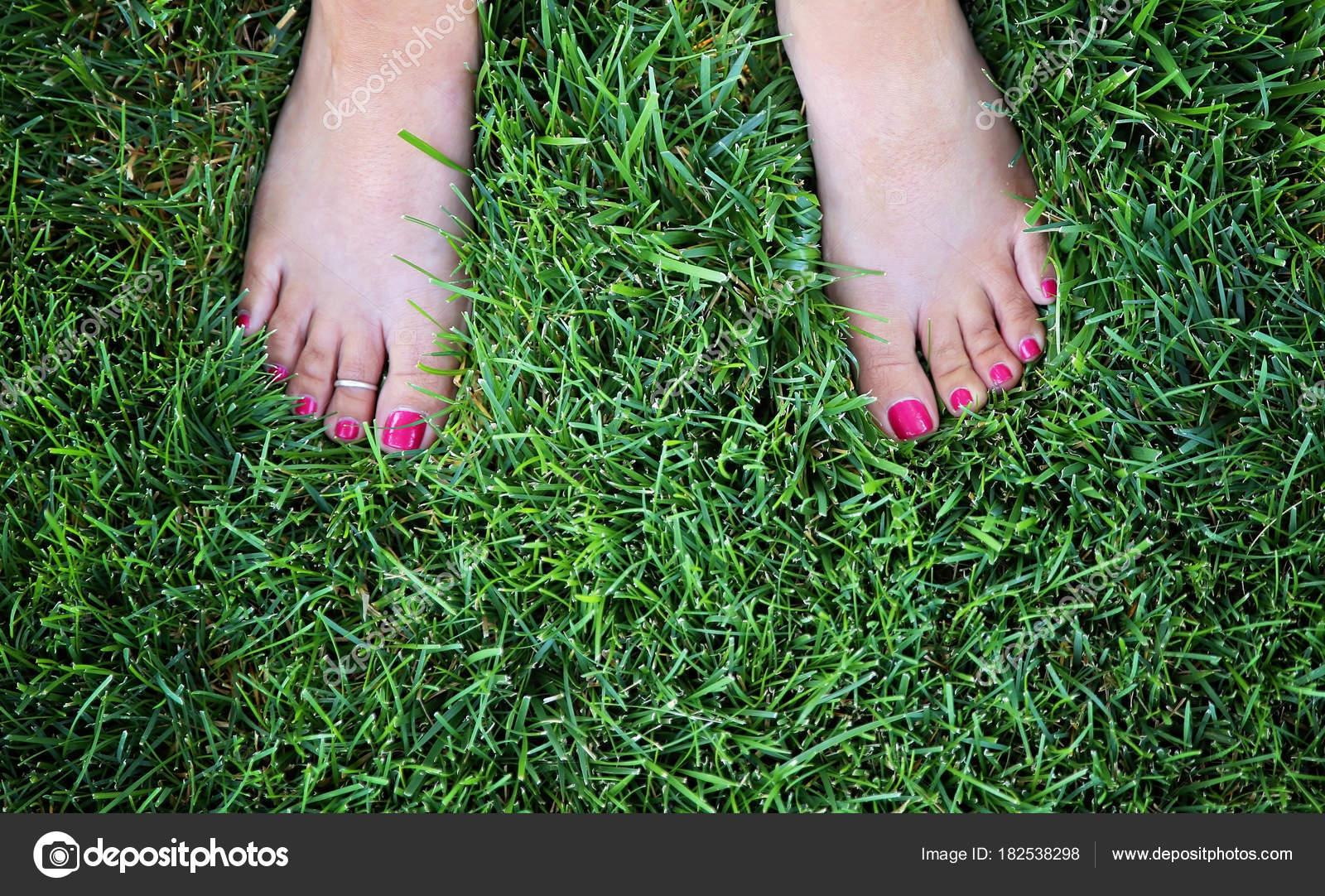 bastante desnudos pies de una mujer de exuberante hierba verde con ...