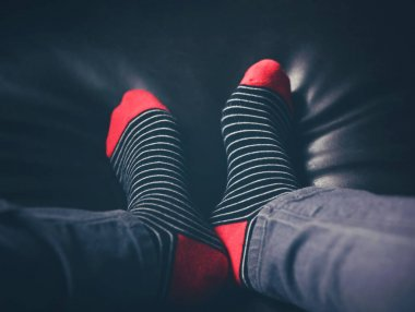 moody photo of black and red striped socks on a couch toned with a matte retro vintage inastagram filter