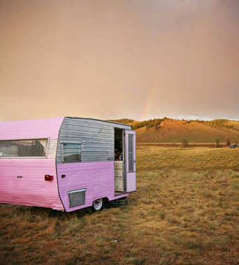cute vintage camper trailer in the sawtooth mountain range in a desolate camp ground during a summer rain storm with a rainbow in the distance toned with a retro vintage instagram filter
