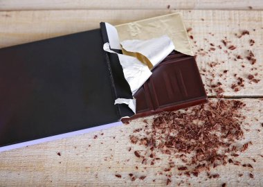 overhead studio shot of a dark chocolate bar in the package with shavings on a wooden background unhealthy food concept