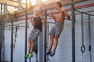 sportive buddies doing pull ups