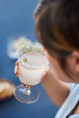 woman holding lemon lavendar cocktail with flower