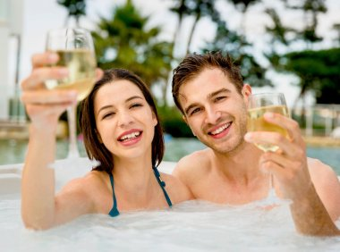 couple in jacuzzi with wineglasses in hands