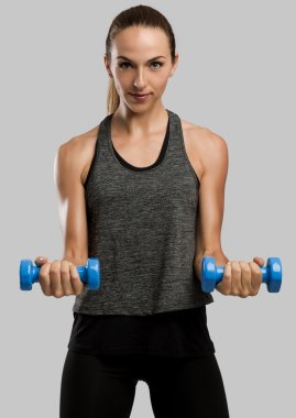Fitness woman with two dumbbells in hands