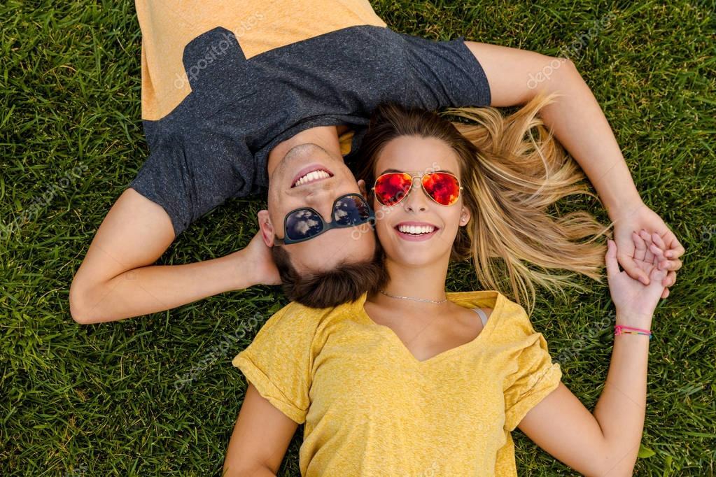 beautiful couple lying on grass