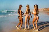tři dívky v plavkách na pláži