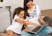 Fotografie Mutter und Tochter arbeiten mit einem Laptop
