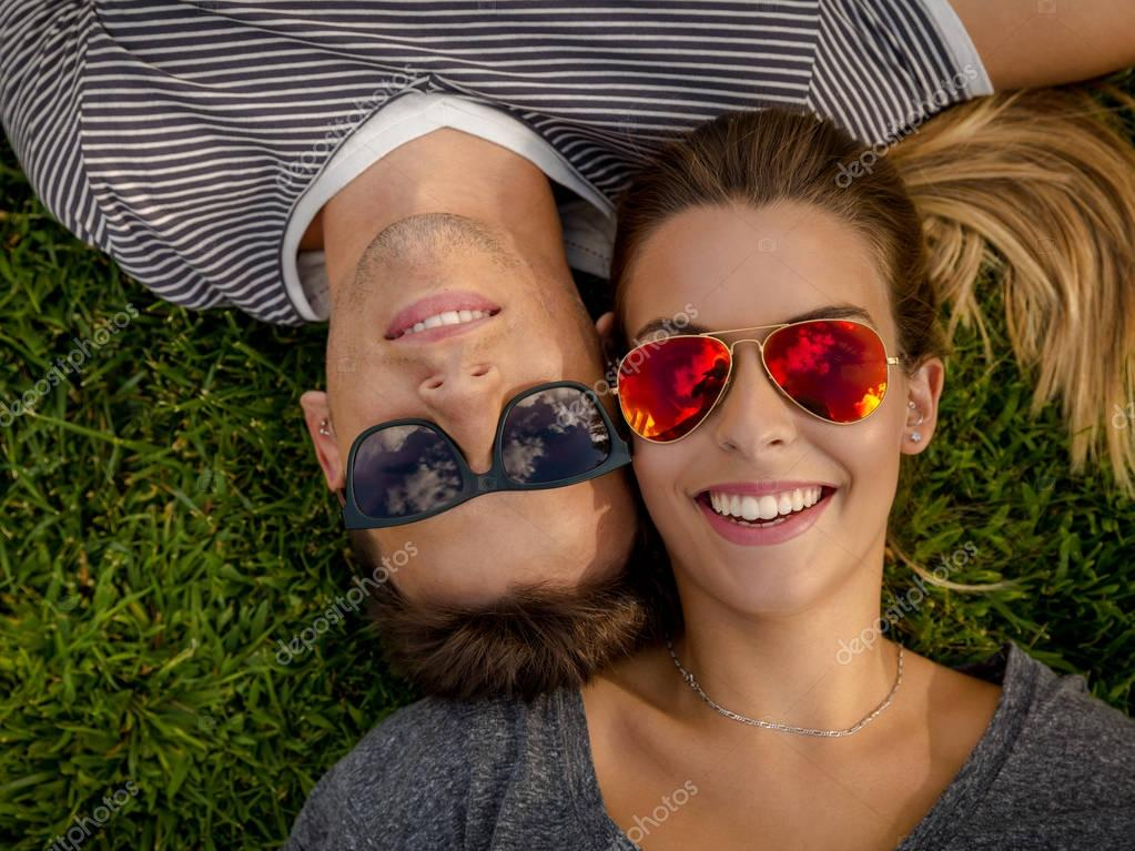 couple in sunglasses lying on grass