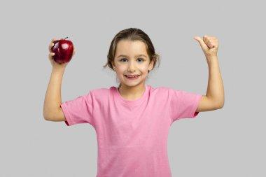 little girl holding red apple