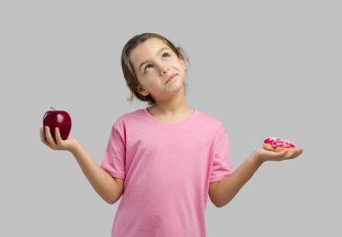 girl choosing between apple and donut