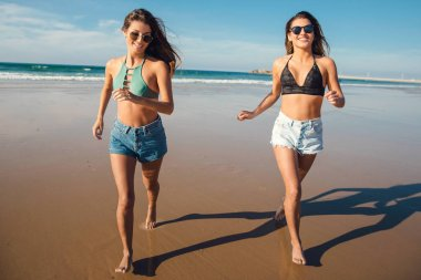 Two female friends in bikini running at the beach and having fun together