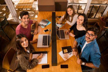Group of friends studying together at bibliotech