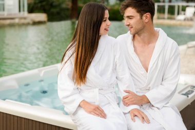Young couple in bathrobes sitting near on jacuzzi in luxury hotel