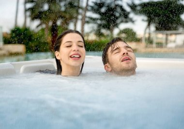 Closeup of young couple relaxing inside jacuzzi in rainy day
