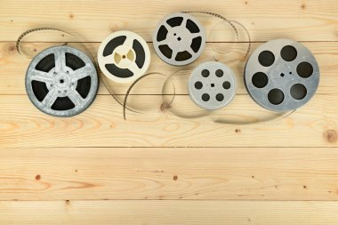 Obsolete cinema films on wooden surface of table. Copy space stock vector