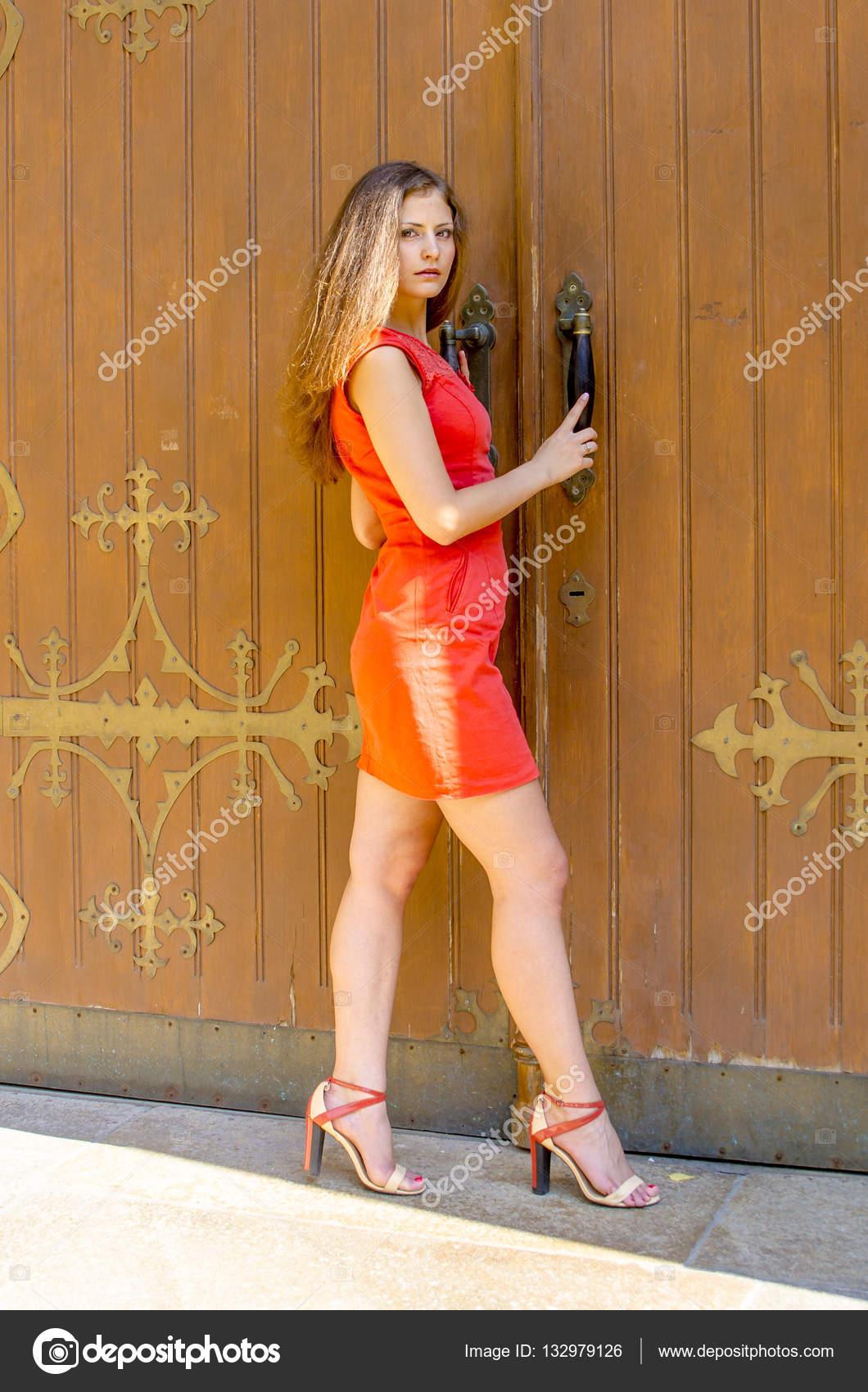 Schöne junge Frau in einem roten Cocktailkleid kurz Fuß vom alten ...