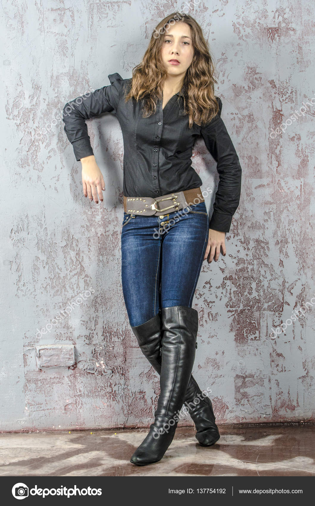 young with curly hair in a black shirt jeans and high boots