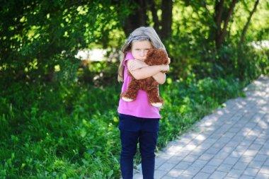 Adorable sad girl with teddy bear in park.