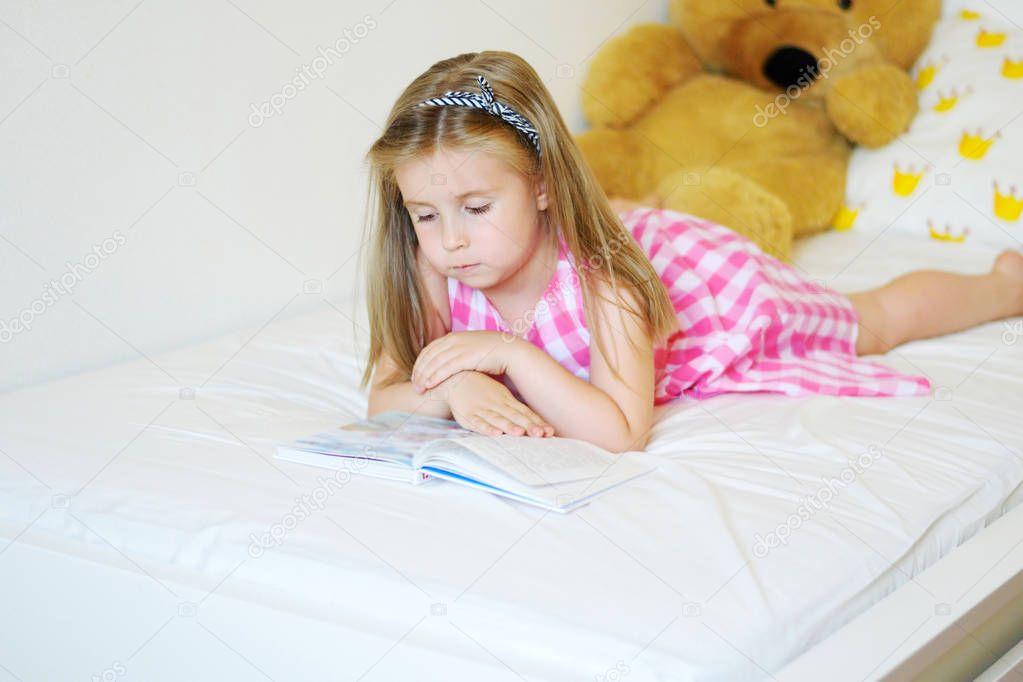 Entzuckende Kleine Madchen Auf Dem Bett Liegen Und Ein Buch Zu Lesen