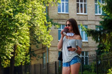 Beautiful stylish girl student drinking coffee on a city street
