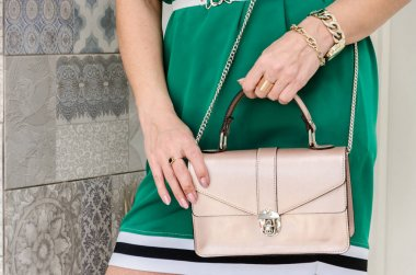 woman is holding a small stylish bag (clutch) of delicate beige