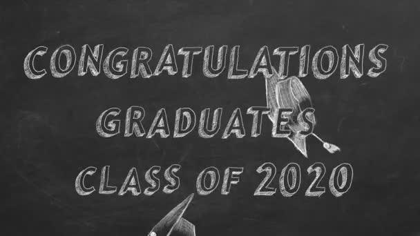Hand drawing text Congratulations graduates. Class of 2020. and graduation caps on blackboard.
