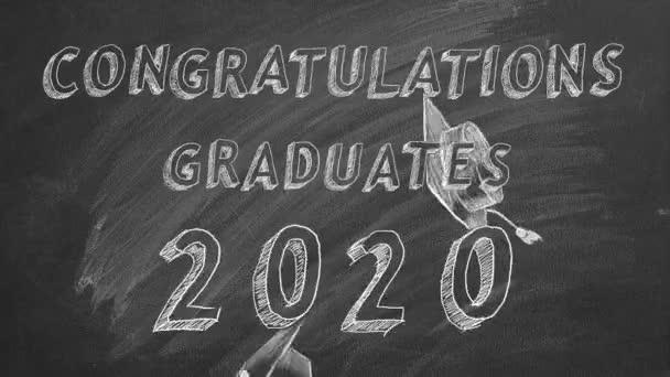 Rukopis Blahopřejeme absolventům. 2020.  a maturitní čepice na tabuli.