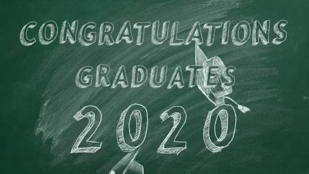Hand drawing text Congratulations graduates.  2020. and graduation caps  on green chalkboard.