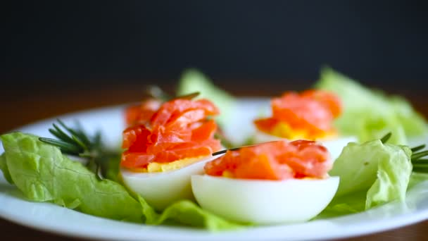 boiled eggs with salted red fish and salad leaves on a wooden table