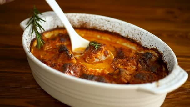 pečené maso s kořeněnou zeleninou a omáčkou v keramické podobě, na dřevěném stole