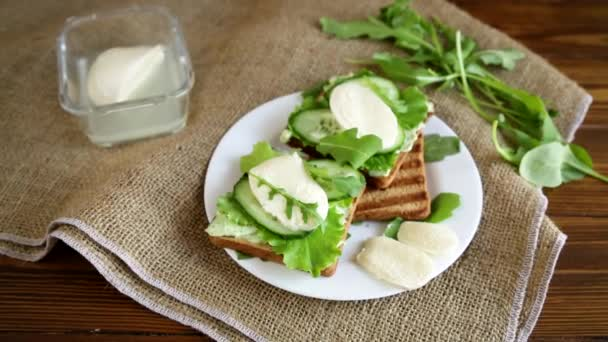 fried bread toasts with salad leaves, cheese spread and mozzarella in a plate