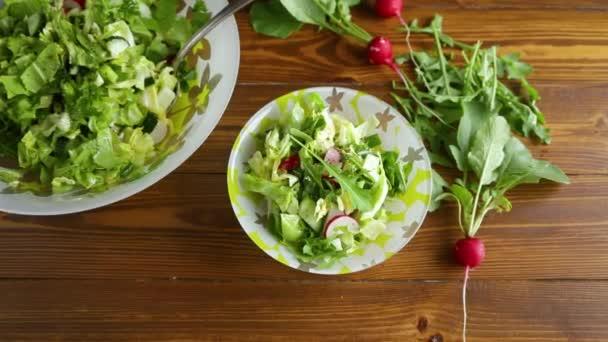 Jarní salát z rané zeleniny, listů salátu, ředkviček a bylinek v talíři na dřevěném stole