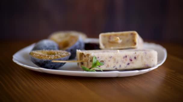 Pflaumensüßes hausgemachtes Eis auf einem Stock mit Pflaumenscheiben im Inneren, in einem Teller