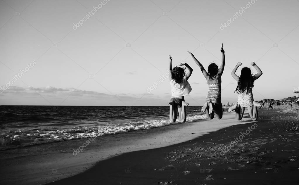 Three girlfriends jumping on the beach