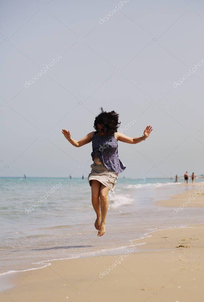 mature woman jumping on beach